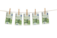 垂悬在白色背景的晒衣绳的100张欧洲钞票 免版税图库摄影