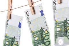 垂悬在白色背景的晒衣绳的100张欧洲钞票 免版税库存图片