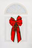 垂悬在白色门的大红色弓 免版税库存照片