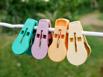 垂悬在白色绳索的五颜六色的服装扣子或晒衣夹 免版税图库摄影