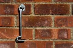 垂悬在砖墙上的门锁环 库存图片