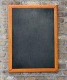 垂悬在砖墙上的年迈的黑板 免版税库存照片