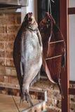 垂悬在砖墙背景的两条大熏制的鱼 免版税库存图片