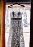垂悬在窗口的婚礼礼服在屋子里 库存照片