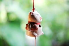 垂悬在窗口的日本幸运的猫玩偶 免版税图库摄影