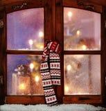 垂悬在窗玻璃的圣诞节围巾 免版税库存图片