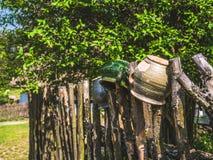 垂悬在篱芭的五颜六色的泥罐 免版税图库摄影
