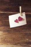 垂悬在精美桃红色发光的心脏板料,测试的一个地方的晒衣夹的一张白色纸片 库存照片