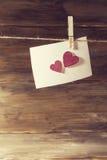 垂悬在精美桃红色发光的心脏板料,测试的一个地方的晒衣夹的一张白色纸片 库存图片