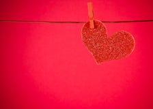 垂悬在红色背景,情人节的概念的装饰红色心脏 库存照片