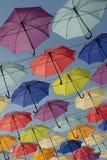 垂悬在绳子蓝天背景的明亮的五颜六色的伞 库存图片