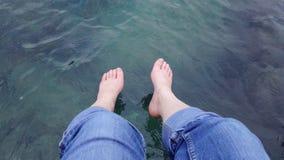 垂悬在绿浪的对白种人脚 库存图片