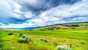 垂悬在肥沃的农地和绵延山的黑暗的云彩沿高速公路5A在Nicola湖附近,在坎卢普斯和梅里特之间 库存照片