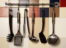 垂悬在色的瓦片墙壁上的厨房器物 库存照片