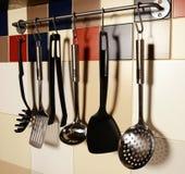 垂悬在色的瓦片墙壁上的厨房器物 免版税图库摄影