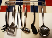 垂悬在色的瓦片墙壁上的厨房器物 库存图片