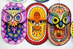 垂悬在艺术学院墙壁上的三个五颜六色的猫头鹰面具 库存照片