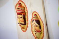 垂悬在艺术学院墙壁上的两个五颜六色的面具 库存图片
