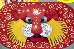 垂悬在艺术学院墙壁上的五颜六色的狮子面具 图库摄影