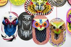 垂悬在艺术学院墙壁上的五颜六色的猫头鹰面具 免版税库存图片
