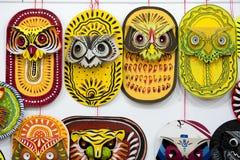 垂悬在艺术学院墙壁上的五颜六色的猫头鹰面具 免版税图库摄影