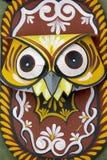 垂悬在艺术学院墙壁上的五颜六色的猫头鹰面具 库存照片