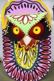 垂悬在艺术学院墙壁上的五颜六色的猫头鹰面具 库存图片