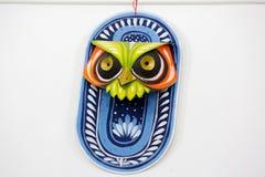 垂悬在艺术学院墙壁上的五颜六色的猫头鹰面具 免版税库存照片