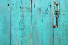 垂悬在葡萄酒小野鸭蓝色木门的古铜色万能钥匙 免版税库存照片