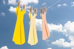垂悬在蓝色夏天天空前面的一条晾衣绳的三件Origami纸礼服(淡色) 免版税库存图片