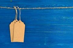垂悬在蓝色背景的一条绳索的三个棕色白纸价牌或标号组 免版税库存照片