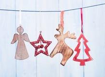 垂悬在蓝色背景的串的老圣诞节装饰 库存照片