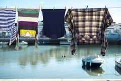 垂悬在街道上的晒衣绳的五颜六色的衣裳 图库摄影
