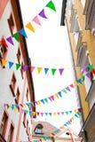 垂悬在街道节日的房子门面的五颜六色的信号旗 免版税图库摄影