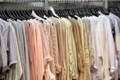 垂悬在衣橱或商店的衣裳行  库存照片