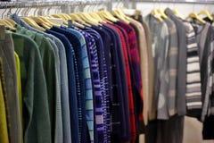 垂悬在衣橱或商店的衣裳行  免版税库存图片