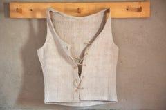 垂悬在衣橱的古色古香的亚麻制汗衫在墙壁 免版税库存图片