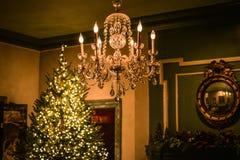 垂悬在被点燃的圣诞树旁边的水晶枝形吊灯 图库摄影