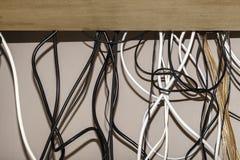 垂悬在计算机书桌后的不整洁缆绳 图库摄影