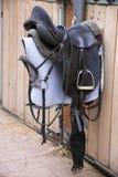 垂悬在谷仓的马术运动的皮革马鞍 免版税库存图片