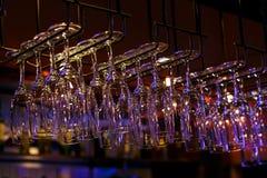 垂悬在酒吧上的酒杯 免版税库存图片