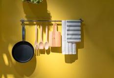 垂悬在金属的厨房器物和毛巾折磨反对黄色 免版税图库摄影