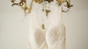 垂悬在金葡萄酒枝形吊灯的一奶油色婚纱的掀动射击 股票视频