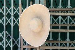 垂悬在钢门前面的木头的宽边缘织法帽子 免版税图库摄影