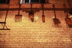 垂悬在铺磁砖的墙壁上的麦芽叉子和铁锹 库存照片