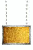 垂悬在链子的发光的金叶箔牌 库存照片