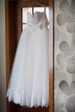垂悬在门的婚礼礼服 免版税库存照片