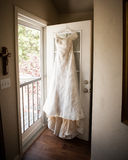 垂悬在门的新娘礼服 免版税图库摄影