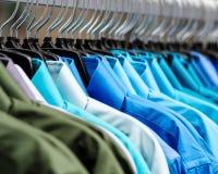 垂悬在颜色的许多衬衣 免版税库存图片