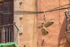 垂悬在高度的一个电缆的一双老鞋 图库摄影